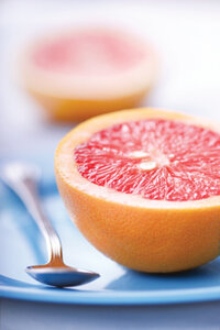 half of a grapefruit with spoon