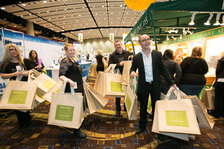 Boldijarre Koronczay and his team pass out bags in front of the Eminence Organic Skin Care booth.