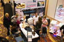 The ClearFX Skin team demonstrating their microdermabrasion equipment in their booth.