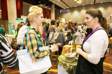 An attendee engages in a discussion with an exhibitor on the expo floor.