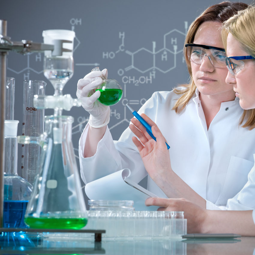 Two female chemists with beakers