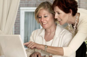 Two women talking and working on a computer