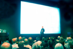 Presenter speaking to a crowd in front of a bright presentation screen