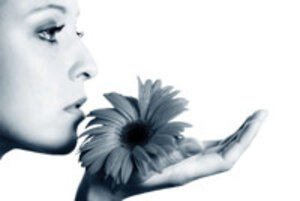 black and white image of woman smelling flower