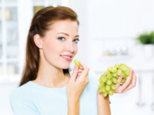 professional skin care client eating antioxidant-rich grapes