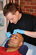 Author Andy Rouillard performs an eyebrow wax on a male client.