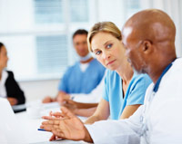 Physicians talking at a conference room table