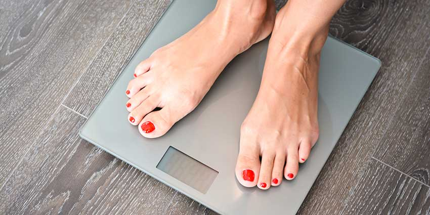 Pedicured woman standing on scale