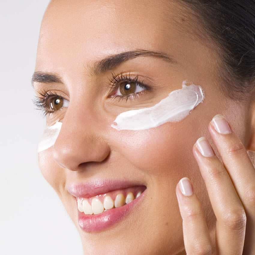 Woman putting lotion under her eye
