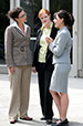 Three professional women in suits, standing outside and speaking to each other