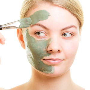 Woman applying clay acne mask