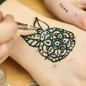 Female hands getting flower black henna tattoo