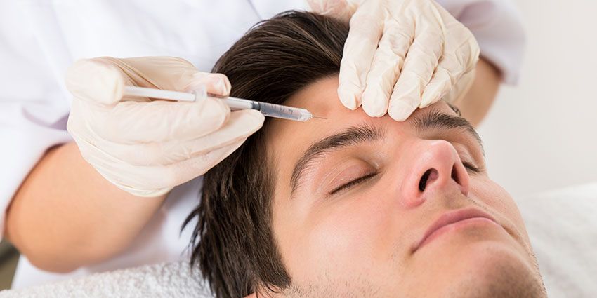 Man receiving esthetic injection in forehead
