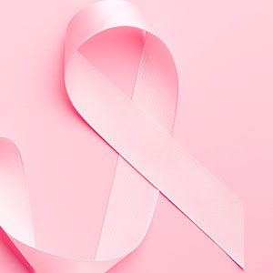 Pink awareness ribbon over pink background