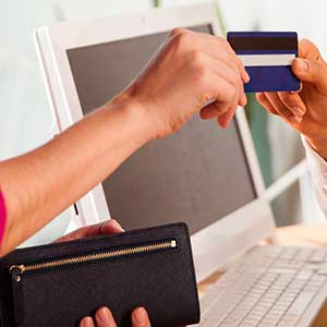 Woman in pink paying with credit card