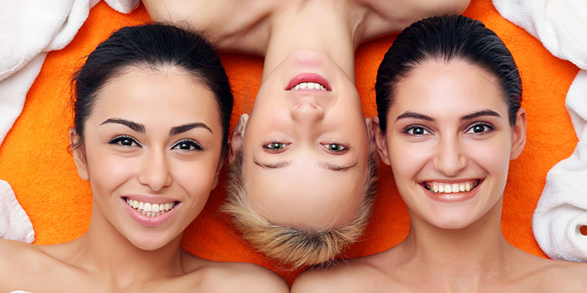 Three smiling women at spa with towels