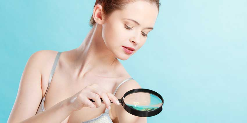 Woman looking at skin in magnifying glass with blue background