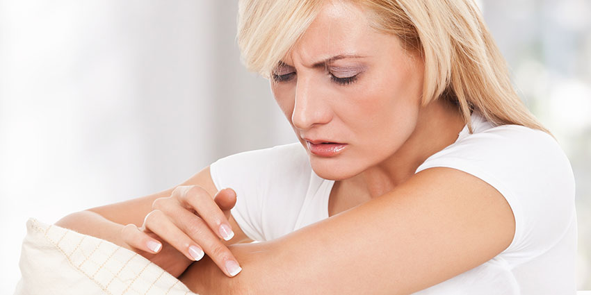 Blonde woman examining skin on arm