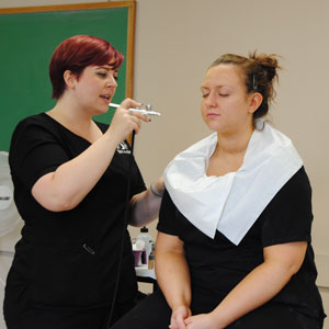 MacKenzie Miller (left) demonstrating airbrush makeup application.