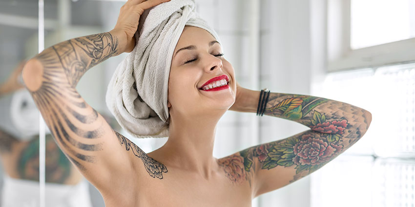 Tattooed woman with clear skin in towel smiling