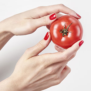 Smooth hands with red nail polish holding tomato