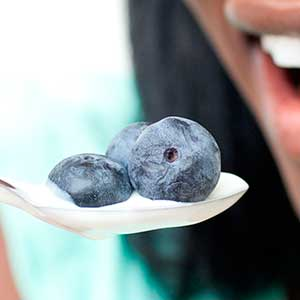 Woman eating yogurt with blueberries