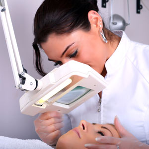 Esthetician with magnifying lamp