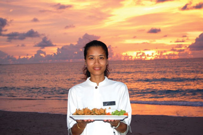 woman with tray of food in front of ocean