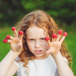 Girl with raspberries on her fingers