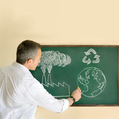 man drawing environmental images on chalkboard