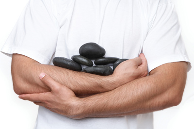 male esthetician carrying stones