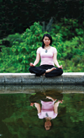 woman meditating next to water