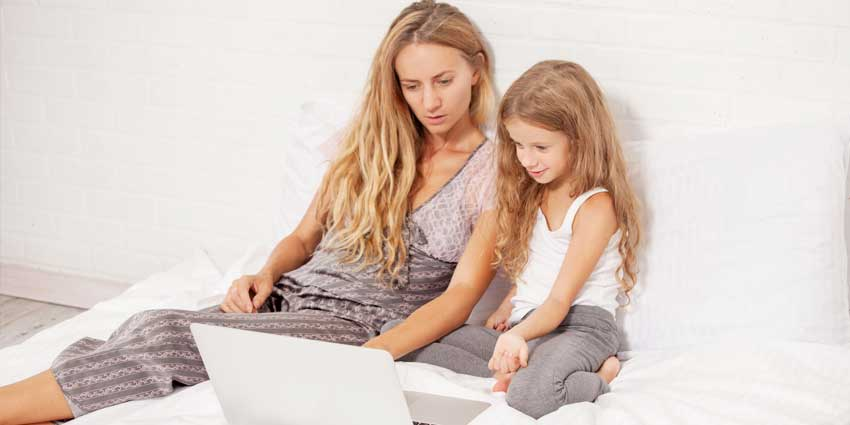 Woman and young girl on computer