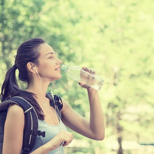 Woman hiking and drinking water