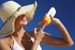 woman in hat getting sunscreen out of bottle